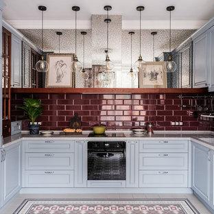Идея дизайна: п-образная кухня среднего размера в классическом стиле с обеденным столом, монолитной раковиной, фасадами с выступающей филенкой, серыми фасадами, столешницей из акрилового камня, красным фартуком, фартуком из керамической плитки, полом из керамогранита, разноцветным полом и черной техникой без острова