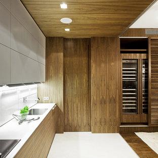 Пример оригинального дизайна: линейная кухня-гостиная в современном стиле с врезной раковиной, плоскими фасадами, фасадами цвета дерева среднего тона, белым фартуком, белым полом и белой столешницей без острова