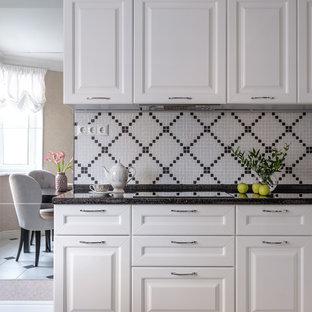 Пример оригинального дизайна: кухня в стиле неоклассика (современная классика) с фасадами с выступающей филенкой, фартуком из плитки мозаики, черной столешницей, белым полом и черно-белыми фасадами