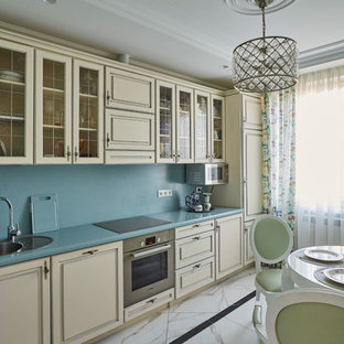 На фото: линейная кухня в стиле современная классика с накладной раковиной, фасадами с выступающей филенкой, бежевыми фасадами, синим фартуком, синей столешницей, обеденным столом, техникой из нержавеющей стали и белым полом без острова с