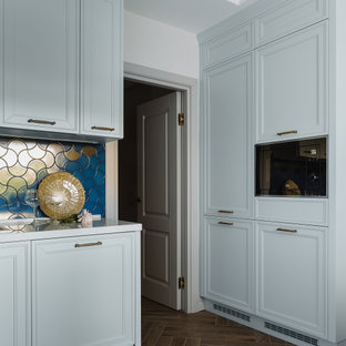 Mid-sized transitional l-shaped separate kitchen in Moscow with a drop-in sink, raised-panel cabinets, turquoise cabinets, quartz benchtops, blue splashback, ceramic splashback, black appliances, porcelain floors, brown floor and white benchtop.