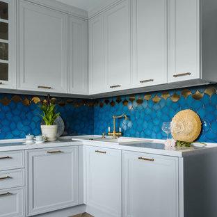 モスクワの中サイズのトランジショナルスタイルのおしゃれなキッチン (ドロップインシンク、レイズドパネル扉のキャビネット、ターコイズのキャビネット、クオーツストーンカウンター、青いキッチンパネル、セラミックタイルのキッチンパネル、黒い調理設備、磁器タイルの床、茶色い床、白いキッチンカウンター) の写真