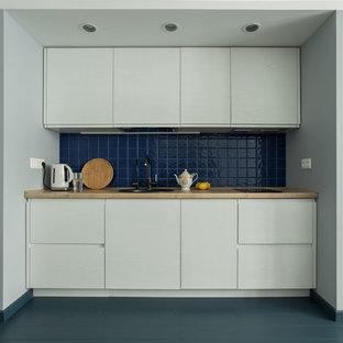 На фото: прямая кухня-гостиная в современном стиле с накладной раковиной, плоскими фасадами, белыми фасадами, синим фартуком и серым полом без острова с