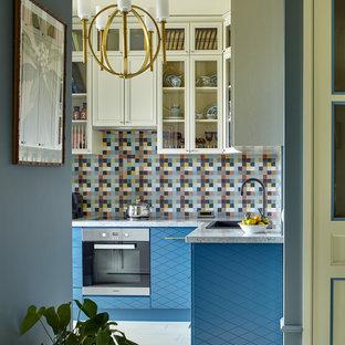 Идея дизайна: угловая кухня-гостиная в стиле современная классика с накладной раковиной, плоскими фасадами, синими фасадами, разноцветным фартуком, техникой из нержавеющей стали и белым полом без острова