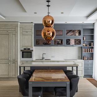 На фото: линейные кухни в современном стиле с накладной раковиной, фасадами с утопленной филенкой, белым фартуком, белой техникой, светлым паркетным полом, островом и бежевым полом
