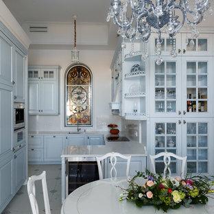 Удачное сочетание для дизайна помещения: п-образная кухня в классическом стиле с обеденным столом, врезной раковиной, фасадами с выступающей филенкой, синими фасадами, белым фартуком, белой техникой и полуостровом - самое интересное для вас