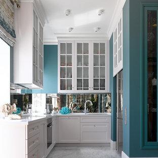 Неиссякаемый источник вдохновения для домашнего уюта: п-образная кухня в морском стиле с фасадами с утопленной филенкой, белыми фасадами, черной техникой, серым полом, белой столешницей, врезной раковиной и фартуком из зеркальной плитки