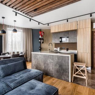 На фото: п-образные кухни-гостиные в современном стиле с врезной раковиной, плоскими фасадами, светлыми деревянными фасадами, коричневым фартуком, черной техникой, полуостровом, коричневым полом, белой столешницей и деревянным потолком