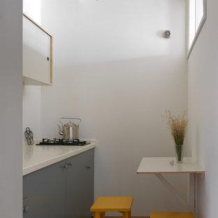 Пример оригинального дизайна: отдельная, прямая кухня в современном стиле с плоскими фасадами, серыми фасадами, белым фартуком и белой столешницей без острова