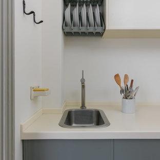 На фото: отдельная, прямая кухня в стиле ретро с накладной раковиной, плоскими фасадами, серыми фасадами, белым фартуком и белой столешницей