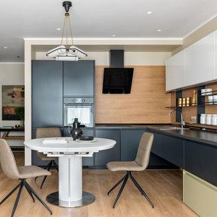 Свежая идея для дизайна: угловая кухня в современном стиле с обеденным столом, накладной раковиной, плоскими фасадами, черными фасадами, бежевым фартуком, фартуком из дерева, техникой под мебельный фасад, светлым паркетным полом, бежевым полом и черной столешницей без острова - отличное фото интерьера