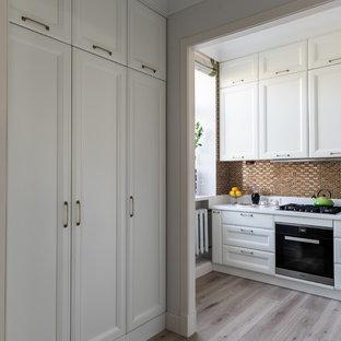 モスクワの中くらいのトランジショナルスタイルのおしゃれなキッチン (アンダーカウンターシンク、レイズドパネル扉のキャビネット、白いキャビネット、人工大理石カウンター、黄色いキッチンパネル、モザイクタイルのキッチンパネル、シルバーの調理設備、ラミネートの床、ベージュの床、白いキッチンカウンター) の写真
