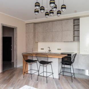 Идея дизайна: линейная кухня-гостиная в современном стиле с врезной раковиной, плоскими фасадами, серыми фасадами, белым фартуком и островом