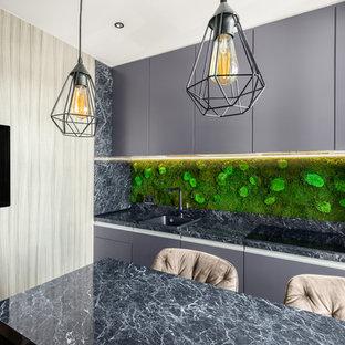 На фото: линейные кухни в современном стиле с накладной раковиной, плоскими фасадами, серыми фасадами, зеленым фартуком, островом и серой столешницей