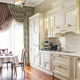 Идея дизайна: большая угловая кухня в классическом стиле с обеденным столом, столешницей из акрилового камня, фартуком из керамической плитки, белой техникой, паркетным полом среднего тона, коричневым полом, фасадами в стиле шейкер, белыми фасадами и белым фартуком без острова
