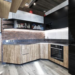 Стильный дизайн: угловая кухня в современном стиле с обеденным столом, врезной раковиной, плоскими фасадами, фасадами цвета дерева среднего тона, коричневым фартуком, фартуком из кирпича, черной техникой и серым полом без острова - последний тренд