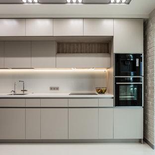 Свежая идея для дизайна: линейная кухня в современном стиле с плоскими фасадами, белым фартуком, фартуком из стекла, черной техникой, белым полом, белой столешницей, одинарной раковиной, бежевыми фасадами и бетонным полом без острова - отличное фото интерьера
