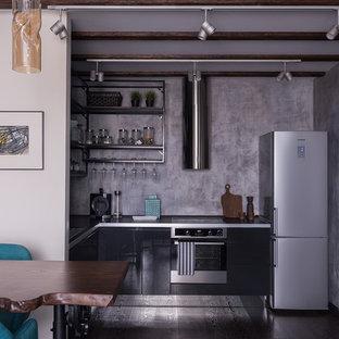 Пример оригинального дизайна: угловая кухня-гостиная в современном стиле с накладной раковиной, плоскими фасадами, черными фасадами, серым фартуком, техникой из нержавеющей стали, темным паркетным полом и коричневым полом без острова