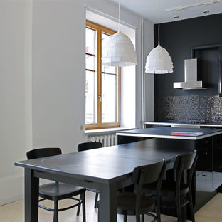 Small contemporary open concept kitchen inspiration - Small trendy galley light wood floor open concept kitchen photo in Moscow with a drop-in sink, flat-panel cabinets, black cabinets, laminate countertops, black backsplash, mosaic tile backsplash, stainless steel appliances and an island