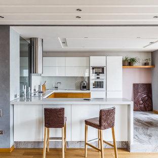 Создайте стильный интерьер: п-образная кухня-гостиная среднего размера в современном стиле с плоскими фасадами, белыми фасадами, столешницей из акрилового камня, белым фартуком, фартуком из плитки мозаики, белой техникой, полом из керамогранита, серым полом, накладной раковиной и полуостровом - последний тренд