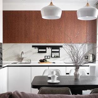 На фото: угловая кухня-гостиная в современном стиле с плоскими фасадами, фасадами цвета дерева среднего тона, белым фартуком, черной техникой, белой столешницей, двойной раковиной и фартуком из каменной плиты с
