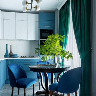 На фото: угловая кухня среднего размера в стиле современная классика с обеденным столом, плоскими фасадами, столешницей из кварцевого агломерата, белым фартуком, фартуком из плитки мозаики, черной техникой, полом из керамогранита, серым полом, синими фасадами и белой столешницей без острова