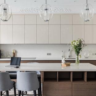 На фото: параллельная кухня среднего размера в современном стиле с врезной раковиной, плоскими фасадами, фасадами цвета дерева среднего тона, серым фартуком, техникой под мебельный фасад, островом, серым полом и серой столешницей с