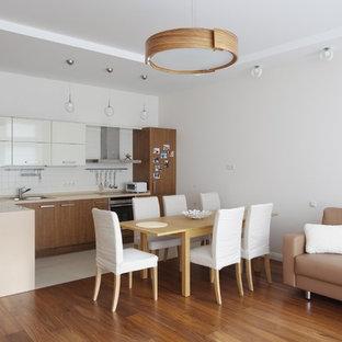 На фото: угловые кухни-гостиные в современном стиле с плоскими фасадами, фасадами цвета дерева среднего тона, белым фартуком и полуостровом