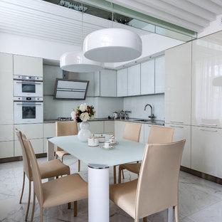 На фото: со средним бюджетом угловые кухни среднего размера в современном стиле с обеденным столом, врезной раковиной, плоскими фасадами, серыми фасадами, гранитной столешницей, белым фартуком, фартуком из стекла, белой техникой, полом из керамической плитки, белым полом и серой столешницей без острова