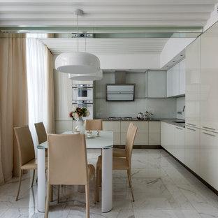 モスクワの広いコンテンポラリースタイルのおしゃれなキッチン (アンダーカウンターシンク、グレーのキャビネット、御影石カウンター、白いキッチンパネル、ガラス板のキッチンパネル、白い調理設備、大理石の床、アイランドなし、フラットパネル扉のキャビネット) の写真