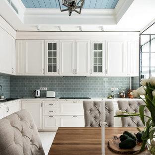 Свежая идея для дизайна: угловая кухня в стиле современная классика с врезной раковиной, белыми фасадами, серым фартуком, черной техникой и белым полом - отличное фото интерьера