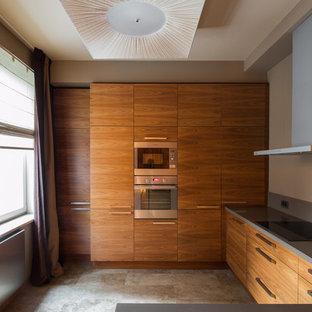 На фото: п-образная кухня-гостиная в современном стиле с плоскими фасадами, фасадами цвета дерева среднего тона, техникой из нержавеющей стали, серым полом и серой столешницей