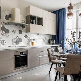 На фото: прямая кухня в современном стиле с обеденным столом, плоскими фасадами, серыми фасадами, разноцветным фартуком, техникой из нержавеющей стали, серым полом и белой столешницей без острова с