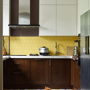 Design ideas for a mid-sized contemporary u-shaped open plan kitchen in Moscow with an undermount sink, flat-panel cabinets, white cabinets, solid surface benchtops, yellow splashback, ceramic splashback, stainless steel appliances, ceramic floors, multi-coloured floor and white benchtop.