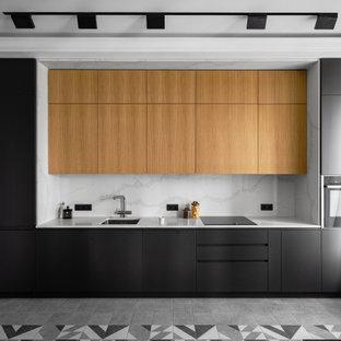 Стильный дизайн: линейная кухня среднего размера в современном стиле с обеденным столом, врезной раковиной, плоскими фасадами, фасадами цвета дерева среднего тона, столешницей из кварцевого агломерата, белым фартуком, фартуком из кварцевого агломерата, черной техникой, полом из керамической плитки, серым полом, белой столешницей и многоуровневым потолком без острова - последний тренд