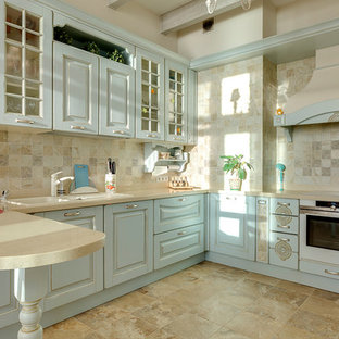 This is an example of a mid-sized country u-shaped separate kitchen in Saint Petersburg with an undermount sink, raised-panel cabinets, turquoise cabinets, solid surface benchtops, beige splashback, ceramic splashback, white appliances, porcelain floors, no island, beige floor and beige benchtop.