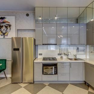 Стильный дизайн: угловая кухня в современном стиле с обеденным столом, плоскими фасадами, серыми фасадами, столешницей из акрилового камня, белым фартуком, белой столешницей и накладной раковиной - последний тренд