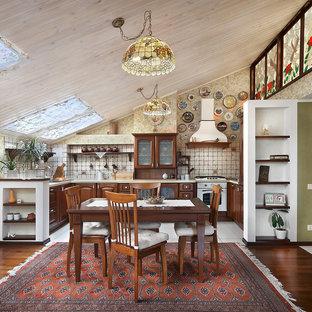 Пример оригинального дизайна: п-образная кухня-гостиная в стиле кантри с темными деревянными фасадами, бежевым фартуком и белой техникой без острова