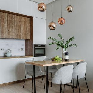 На фото: линейная кухня в современном стиле с обеденным столом, плоскими фасадами, белыми фасадами, столешницей из дерева, белым фартуком, черной техникой, светлым паркетным полом и бежевым полом без острова с