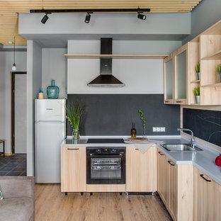 Идея дизайна: угловая кухня-гостиная в скандинавском стиле с накладной раковиной, светлыми деревянными фасадами, черным фартуком, черной техникой, светлым паркетным полом, серой столешницей и бежевым полом без острова