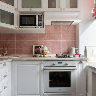 This is an example of a small contemporary l-shaped kitchen in Saint Petersburg with a drop-in sink, glass-front cabinets, white cabinets, pink splashback, white appliances, dark hardwood floors, brown floor and beige benchtop.