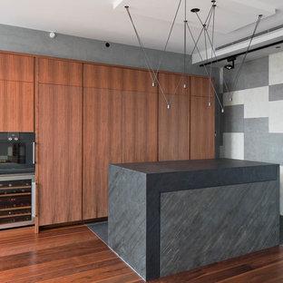 Создайте стильный интерьер: линейная кухня-гостиная в современном стиле с плоскими фасадами, фасадами цвета дерева среднего тона, черной техникой, паркетным полом среднего тона, островом и коричневым полом - последний тренд