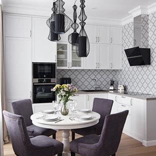 Modelo de cocina comedor en L, tradicional renovada, con fregadero encastrado, armarios estilo shaker, puertas de armario blancas, salpicadero multicolor, electrodomésticos negros, suelo de madera clara y encimeras grises