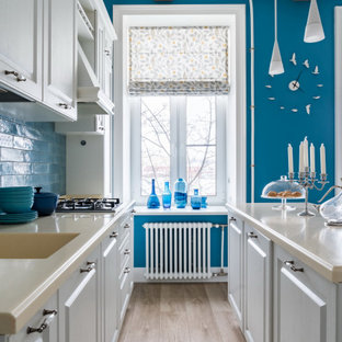 Inspiration for a mid-sized transitional galley kitchen in Saint Petersburg with an integrated sink, raised-panel cabinets, grey cabinets, blue splashback, panelled appliances, with island, beige floor and beige benchtop.