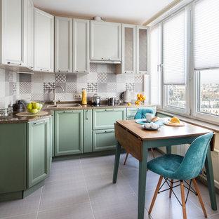 Идея дизайна: угловая кухня в стиле современная классика с обеденным столом, накладной раковиной, фасадами с утопленной филенкой, зелеными фасадами, серым фартуком и бежевым полом без острова