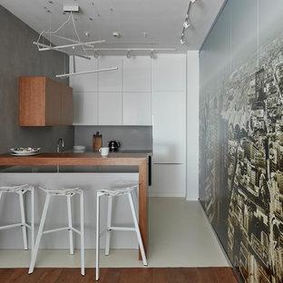 Свежая идея для дизайна: п-образная кухня-гостиная в современном стиле с плоскими фасадами, белыми фасадами, столешницей из дерева, серым фартуком, техникой под мебельный фасад, полуостровом и бежевым полом - отличное фото интерьера