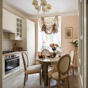 На фото: отдельные кухни в классическом стиле с белыми фасадами, бежевым фартуком и техникой из нержавеющей стали без острова