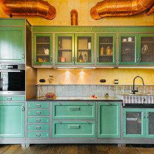 Новый формат декора квартиры: линейная кухня в стиле лофт с раковиной в стиле кантри, фасадами с утопленной филенкой, зелеными фасадами, техникой из нержавеющей стали, коричневым полом и черной столешницей