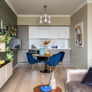 Создайте стильный интерьер: линейная кухня-гостиная среднего размера в современном стиле с монолитной раковиной, серыми фасадами, столешницей из акрилового камня, белым фартуком, фартуком из каменной плиты, черной техникой, светлым паркетным полом, бежевым полом, белой столешницей и фасадами с утопленной филенкой - последний тренд