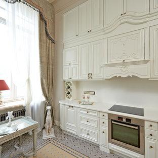 На фото: отдельные, линейные кухни в классическом стиле с накладной раковиной, фасадами с выступающей филенкой, белыми фасадами, белым фартуком и техникой из нержавеющей стали без острова